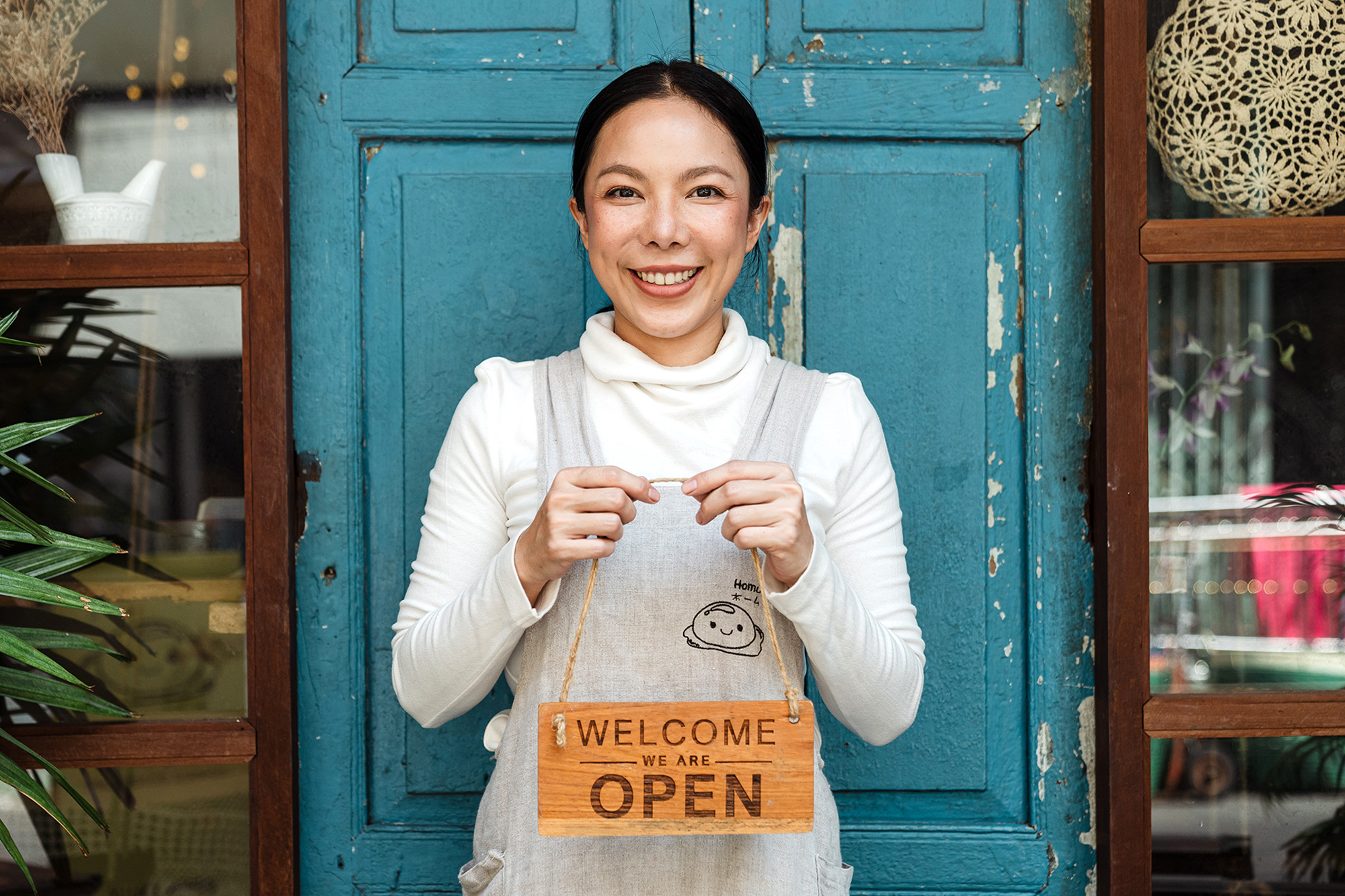 Small business owner holding up a welcome sign